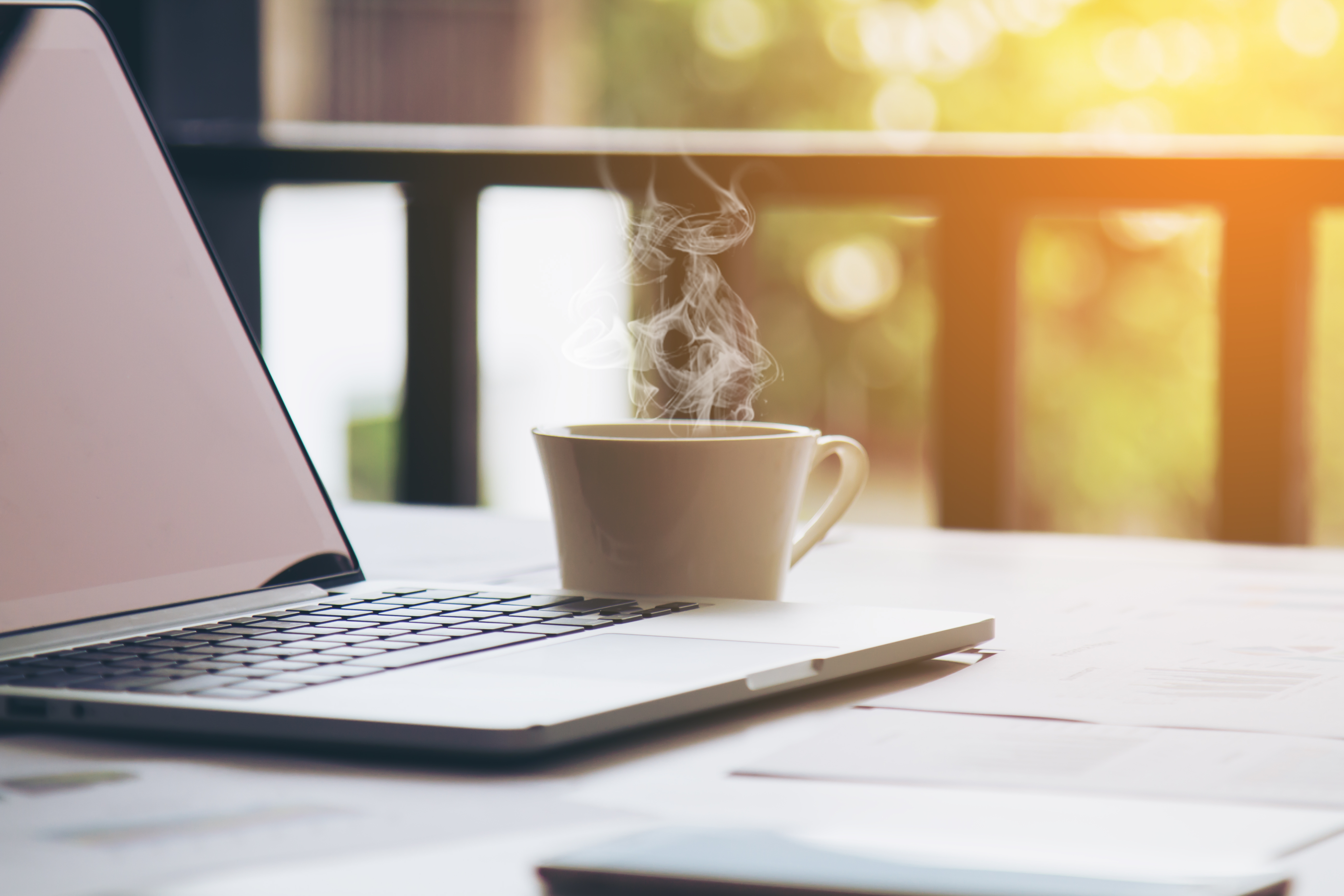 Hot coffee next to a mac laptop in sunlight morning